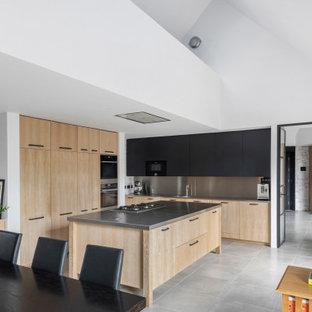 Exemple d'une grande cuisine américaine tendance en L avec un évier 2 bacs, un placard à porte plane, des portes de placard en bois clair, un plan de travail en inox, une crédence grise, une crédence en dalle métallique, un électroménager noir, un sol en carrelage de céramique, un îlot central, un sol gris et un plan de travail gris.