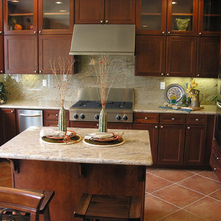Mid-sized southwestern eat-in kitchen ideas - Mid-sized southwest u-shaped terra-cotta floor eat-in kitchen photo in New York with dark wood cabinets, limestone countertops, beige backsplash, stainless steel appliances, an island and glass-front cabinets