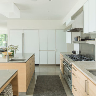 Inspiration for a mid-sized scandinavian galley kitchen in New York with an undermount sink, flat-panel cabinets, light wood cabinets, stainless steel benchtops, stainless steel appliances, concrete floors and multiple islands.