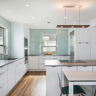 Contemporary eat-in kitchen remodeling - Trendy medium tone wood floor eat-in kitchen photo in Tampa with a single-bowl sink, flat-panel cabinets, white cabinets, glass sheet backsplash, stainless steel appliances, a peninsula and gray countertops