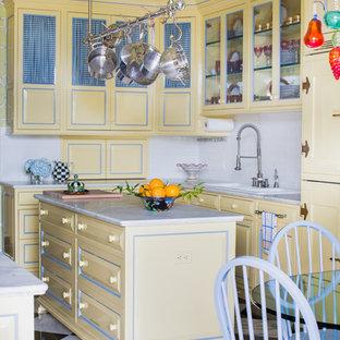 他の地域のヴィクトリアン調のおしゃれなキッチン (レイズドパネル扉のキャビネット、黄色いキャビネット、白いキッチンパネル) の写真
