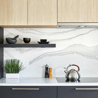 Inredning av ett modernt mellanstort vit linjärt vitt kök och matrum, med en trippel diskho, släta luckor, svarta skåp, bänkskiva i kvarts, vitt stänkskydd, rostfria vitvaror, mellanmörkt trägolv, en köksö och grått golv