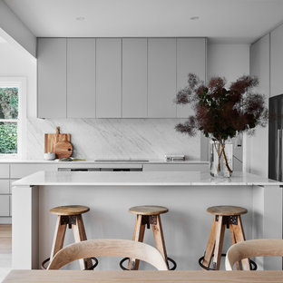 Inspiration for a large contemporary u-shaped eat-in kitchen in Wollongong with grey cabinets, marble benchtops, marble splashback, stainless steel appliances, with island, flat-panel cabinets, white splashback, medium hardwood floors, brown floor, white benchtop and a double-bowl sink.