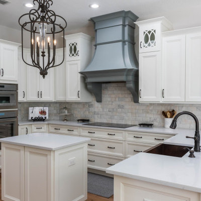 Mid-sized elegant u-shaped medium tone wood floor and brown floor open concept kitchen photo in Orlando with a farmhouse sink, recessed-panel cabinets, white cabinets, quartz countertops, gray backsplash, subway tile backsplash, stainless steel appliances, an island and white countertops
