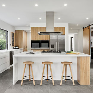 Photo of a scandinavian l-shaped kitchen in Other with an undermount sink, flat-panel cabinets, light wood cabinets, stainless steel appliances, with island, grey floor and white benchtop.