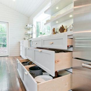 Zweizeilige, Mittelgroße Landhausstil Wohnküche mit Landhausspüle, Schrankfronten im Shaker-Stil, weißen Schränken, Marmor-Arbeitsplatte, Küchenrückwand in Weiß, Rückwand aus Holz, Küchengeräten aus Edelstahl, gebeiztem Holzboden und Kücheninsel in Los Angeles