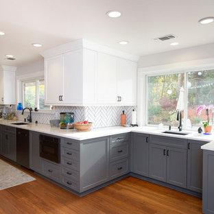広いトランジショナルスタイルのおしゃれなキッチン (アンダーカウンターシンク、シェーカースタイル扉のキャビネット、白いキャビネット、クオーツストーンカウンター、白いキッチンパネル、サブウェイタイルのキッチンパネル、シルバーの調理設備、竹フローリング、アイランドなし、茶色い床、白いキッチンカウンター) の写真