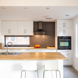 Design ideas for a large contemporary single-wall kitchen/diner in Ottawa with a double-bowl sink, flat-panel cabinets, white cabinets, brown splashback, concrete flooring, wood worktops, glass sheet splashback, stainless steel appliances and an island.