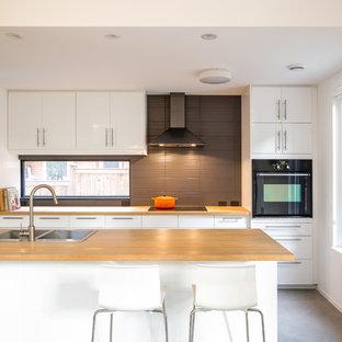 Стильный дизайн: большая прямая кухня в современном стиле с двойной раковиной, плоскими фасадами, белыми фасадами, коричневым фартуком, бетонным полом, обеденным столом, деревянной столешницей, фартуком из стекла, техникой из нержавеющей стали и островом - последний тренд