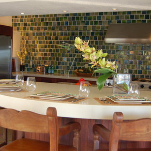 Photo of a tropical galley eat-in kitchen with an undermount sink, louvered cabinets, medium wood cabinets, solid surface benchtops, green splashback, ceramic splashback, stainless steel appliances and with island.