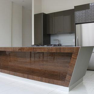 Esempio di una cucina moderna di medie dimensioni con lavello sottopiano, ante lisce, ante marroni, top in superficie solida, paraspruzzi grigio, paraspruzzi con lastra di vetro, elettrodomestici in acciaio inossidabile, pavimento in legno verniciato e isola