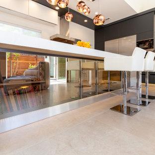 На фото: с высоким бюджетом большие угловые кухни-гостиные в стиле модернизм с накладной раковиной, плоскими фасадами, черными фасадами, гранитной столешницей, оранжевым фартуком, фартуком из стеклянной плитки, техникой из нержавеющей стали, полом из керамической плитки, островом, белым полом и белой столешницей