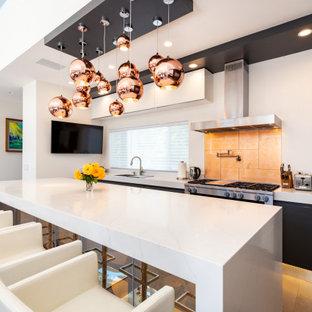Свежая идея для дизайна: большая угловая кухня-гостиная в стиле модернизм с накладной раковиной, плоскими фасадами, черными фасадами, гранитной столешницей, оранжевым фартуком, фартуком из стеклянной плитки, техникой из нержавеющей стали, полом из керамической плитки, островом, белым полом и белой столешницей - отличное фото интерьера