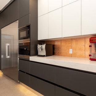 サンフランシスコの広いモダンスタイルのおしゃれなキッチン (ドロップインシンク、フラットパネル扉のキャビネット、黒いキャビネット、御影石カウンター、オレンジのキッチンパネル、ガラスタイルのキッチンパネル、シルバーの調理設備、セラミックタイルの床、白い床、白いキッチンカウンター) の写真