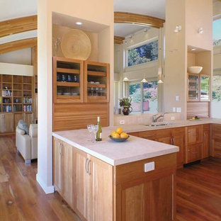 Photo of a contemporary open plan kitchen in San Francisco with shaker cabinets, an undermount sink, light wood cabinets and limestone benchtops.