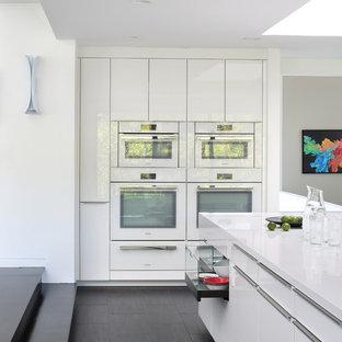 Diseño de cocina comedor actual, grande, con armarios con paneles lisos, puertas de armario blancas, electrodomésticos blancos, una isla, encimera de cuarzo compacto, salpicadero rojo, salpicadero de vidrio templado y suelo de baldosas de porcelana