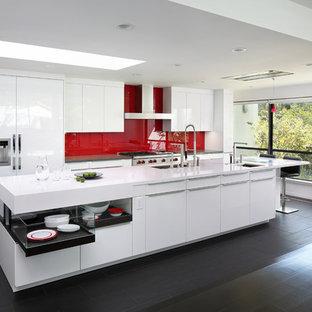 Bild på ett funkis parallellkök, med släta luckor, vita skåp, rött stänkskydd, glaspanel som stänkskydd och en köksö