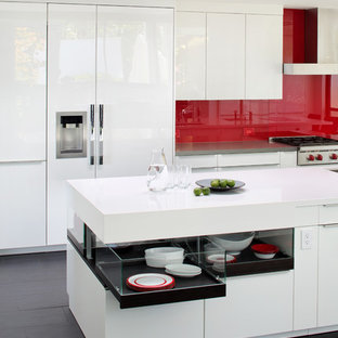 Large contemporary eat-in kitchen inspiration - Example of a large trendy porcelain floor eat-in kitchen design in San Francisco with an undermount sink, flat-panel cabinets, white cabinets, quartz countertops, red backsplash, glass sheet backsplash, white appliances and an island