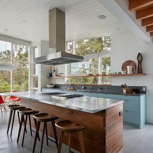 Idee per una cucina moderna con ante lisce, ante blu, isola, pavimento grigio e top grigio