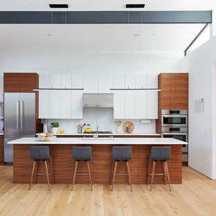 This is an example of a midcentury kitchen in San Francisco with an undermount sink, flat-panel cabinets, white cabinets, white splashback, stainless steel appliances, light hardwood floors, with island and white benchtop.