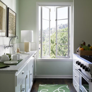Small traditional enclosed kitchen pictures - Example of a small classic galley dark wood floor enclosed kitchen design in Los Angeles with an undermount sink, white backsplash, stainless steel appliances, shaker cabinets, white cabinets, no island and quartz countertops