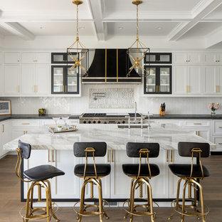 Неиссякаемый источник вдохновения для домашнего уюта: п-образная кухня в стиле современная классика с обеденным столом, врезной раковиной, фасадами с утопленной филенкой, белыми фасадами, белым фартуком, фартуком из плитки мозаики, техникой под мебельный фасад, паркетным полом среднего тона, островом, коричневым полом и белой столешницей