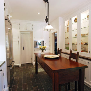 Kitchen - cottage slate floor kitchen idea in Los Angeles with glass-front cabinets and stainless steel appliances