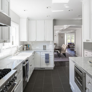 This is an example of a mid-sized transitional galley separate kitchen in Los Angeles with a farmhouse sink, shaker cabinets, white cabinets, quartz benchtops, white splashback, subway tile splashback, stainless steel appliances, ceramic floors, no island and black floor.