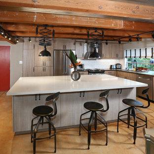 Bild på ett mellanstort industriellt kök, med en trippel diskho, släta luckor, bruna skåp, bänkskiva i koppar, vitt stänkskydd, stänkskydd i tunnelbanekakel, rostfria vitvaror, skiffergolv och en köksö