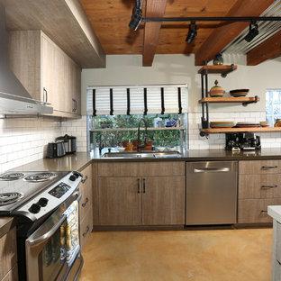 ロサンゼルスの中サイズのインダストリアルスタイルのおしゃれなキッチン (トリプルシンク、フラットパネル扉のキャビネット、茶色いキャビネット、人工大理石カウンター、白いキッチンパネル、サブウェイタイルのキッチンパネル、シルバーの調理設備、スレートの床) の写真