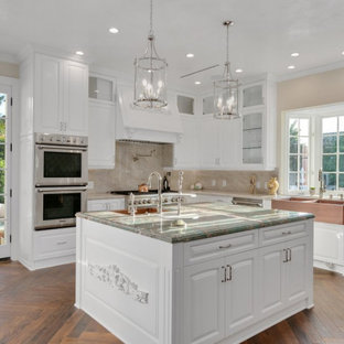 This is an example of a large transitional u-shaped separate kitchen in Los Angeles with a farmhouse sink, shaker cabinets, white cabinets, marble benchtops, beige splashback, marble splashback, stainless steel appliances, dark hardwood floors, multiple islands, multi-coloured floor and turquoise benchtop.