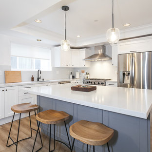This is an example of a mid-sized modern l-shaped eat-in kitchen in Los Angeles with an undermount sink, beaded inset cabinets, white cabinets, quartz benchtops, white splashback, porcelain splashback, stainless steel appliances, vinyl floors, with island, brown floor and white benchtop.