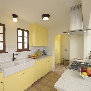 Idéer för mellanstora medelhavsstil kök, med skåp i shakerstil, gula skåp, bänkskiva i kvarts, vitt stänkskydd, stänkskydd i tunnelbanekakel, integrerade vitvaror, en rustik diskho, klinkergolv i terrakotta och en halv köksö