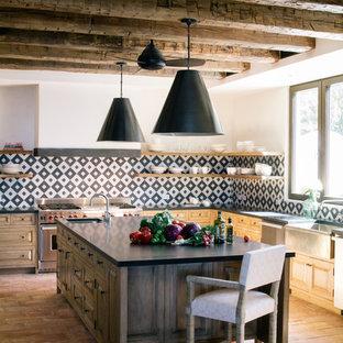 На фото: угловая кухня-гостиная в средиземноморском стиле с раковиной в стиле кантри, открытыми фасадами, светлыми деревянными фасадами, разноцветным фартуком, техникой из нержавеющей стали, полом из терракотовой плитки, островом и розовым полом с