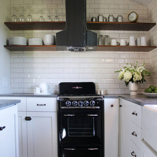 Traditional kitchen inspiration - Inspiration for a timeless kitchen remodel in Los Angeles with a farmhouse sink, open cabinets, white cabinets, white backsplash, subway tile backsplash, black appliances and limestone countertops