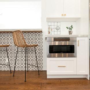 ロサンゼルスの大きいエクレクティックスタイルのおしゃれなキッチン (ドロップインシンク、シェーカースタイル扉のキャビネット、白いキャビネット、クオーツストーンカウンター、白いキッチンパネル、セラミックタイルのキッチンパネル、シルバーの調理設備の、無垢フローリング、茶色い床、グレーのキッチンカウンター) の写真