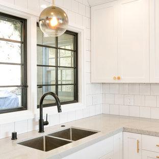 ロサンゼルスの広いエクレクティックスタイルのおしゃれなキッチン (ドロップインシンク、シェーカースタイル扉のキャビネット、白いキャビネット、クオーツストーンカウンター、白いキッチンパネル、セラミックタイルのキッチンパネル、シルバーの調理設備、無垢フローリング、茶色い床、グレーのキッチンカウンター) の写真