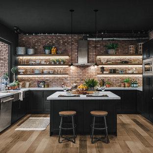 Diseño de cocina en U, industrial, con fregadero sobremueble, armarios estilo shaker, puertas de armario negras, salpicadero rojo, salpicadero de ladrillos, electrodomésticos de acero inoxidable, suelo de madera clara, una isla y encimeras blancas