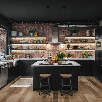 Inspiration for an industrial u-shaped light wood floor kitchen remodel with a farmhouse sink, shaker cabinets, black cabinets, red backsplash, brick backsplash, stainless steel appliances, an island and white countertops