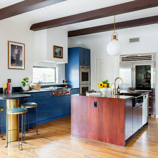 Contemporary kitchen ideas - Trendy l-shaped medium tone wood floor and brown floor kitchen photo in Los Angeles with a farmhouse sink, shaker cabinets, soapstone countertops, black backsplash, stone slab backsplash, stainless steel appliances, an island and blue cabinets