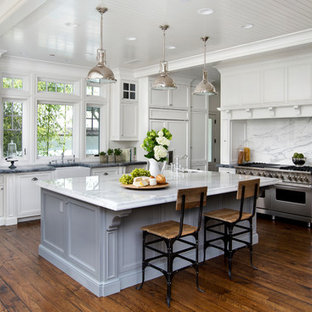 Large trendy l-shaped dark wood floor and brown floor kitchen photo in San Francisco with a farmhouse sink, beaded inset cabinets, white cabinets, marble countertops, white backsplash, stone slab backsplash, paneled appliances and an island