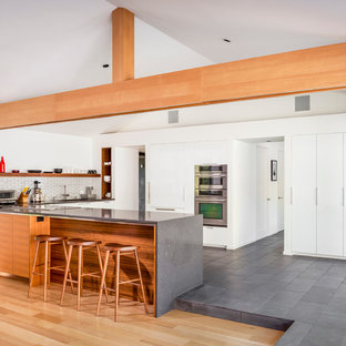 Danish l-shaped slate floor and gray floor eat-in kitchen photo in San Francisco with an undermount sink, flat-panel cabinets, white cabinets, quartzite countertops, white backsplash, subway tile backsplash, stainless steel appliances and a peninsula