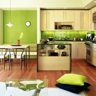 This is an example of a modern l-shaped eat-in kitchen in San Francisco with stainless steel appliances, an undermount sink, flat-panel cabinets, light wood cabinets and green splashback.
