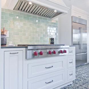 ロサンゼルスの中くらいのエクレクティックスタイルのおしゃれなキッチン (アンダーカウンターシンク、落し込みパネル扉のキャビネット、白いキャビネット、クオーツストーンカウンター、緑のキッチンパネル、セラミックタイルのキッチンパネル、シルバーの調理設備、磁器タイルの床、マルチカラーの床、グレーのキッチンカウンター) の写真