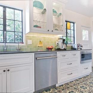 ロサンゼルスの中サイズのエクレクティックスタイルのおしゃれなキッチン (アンダーカウンターシンク、落し込みパネル扉のキャビネット、白いキャビネット、クオーツストーンカウンター、緑のキッチンパネル、セラミックタイルのキッチンパネル、シルバーの調理設備の、磁器タイルの床、マルチカラーの床、グレーのキッチンカウンター) の写真