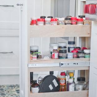 ロサンゼルスの中サイズのエクレクティックスタイルのおしゃれなキッチン (アンダーカウンターシンク、落し込みパネル扉のキャビネット、白いキャビネット、クオーツストーンカウンター、緑のキッチンパネル、セラミックタイルのキッチンパネル、シルバーの調理設備、磁器タイルの床、マルチカラーの床、グレーのキッチンカウンター) の写真