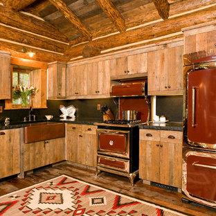 Immagine di una cucina a L rustica con lavello stile country, ante lisce, ante in legno scuro, paraspruzzi nero, paraspruzzi in lastra di pietra, elettrodomestici colorati, parquet scuro e nessuna isola