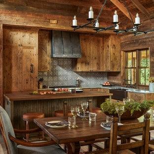 Foto di una cucina rustica con lavello stile country, ante in legno scuro, paraspruzzi grigio, isola, top grigio e parquet chiaro