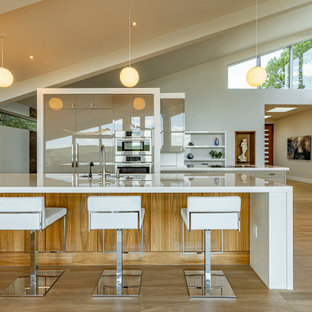This is an example of a large midcentury galley open plan kitchen in Austin with an undermount sink, flat-panel cabinets, grey cabinets, quartz benchtops, white splashback, stainless steel appliances, light hardwood floors, multiple islands, beige floor and white benchtop.