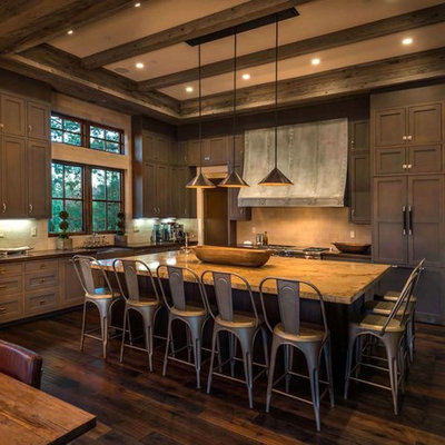 Example of a mountain style l-shaped dark wood floor eat-in kitchen design in Sacramento with shaker cabinets, dark wood cabinets, beige backsplash, paneled appliances and an island